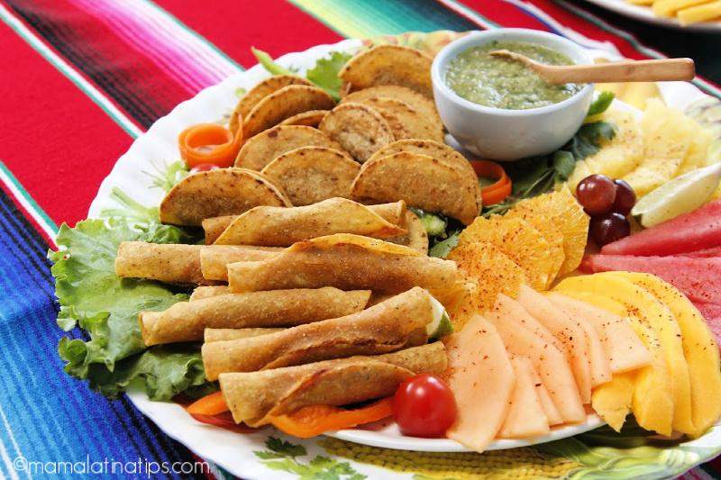 un platón con taquitos dorados, fruta y salsa verde