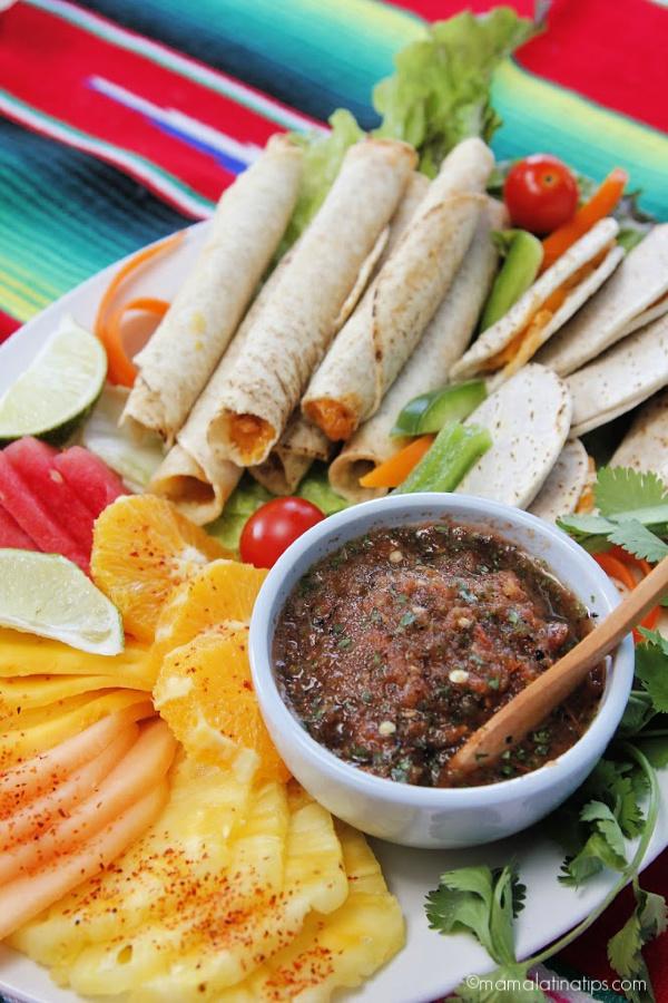 Un platón con taquitos en tortilla de harina, fruta con chile y salsa roja