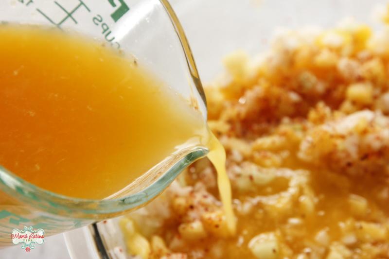 Vaciando jugo de naranja sobre fruta picada