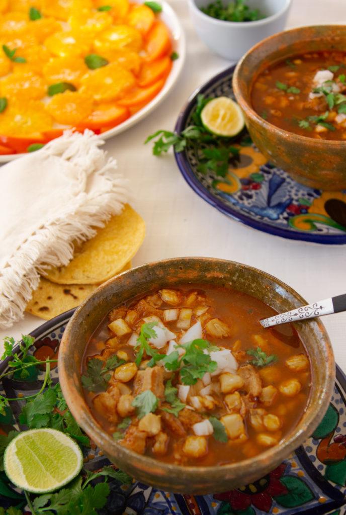dos platos de barro con menudo acompañado con limón, tortillas y ensalada. Con que servir el Menudo